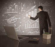 Businessman drawing sales charts on wall Stock Images