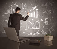 Businessman drawing sales charts on wall Stock Photo