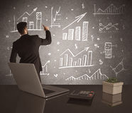 Businessman drawing sales charts on wall Royalty Free Stock Photos