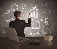 Businessman drawing sales charts on wall Stock Photography