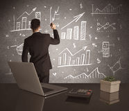 Businessman drawing sales charts on wall Royalty Free Stock Photo
