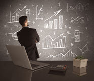 Businessman drawing sales charts on wall Royalty Free Stock Images