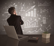 Businessman drawing sales charts on wall Stock Image