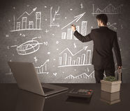 Businessman drawing sales charts on wall. A young marketing office worker drawing pie chart and graph on wall at financial meeting concept Royalty Free Stock Photo