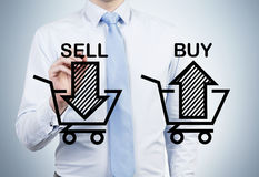 Businessman is drawing 'sell and buy' arrows on the glass screen. Stock Images