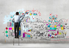 Businessman drawing sketch. Back view of businessman drawing sketch on wall Stock Photography