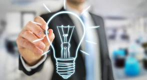 Businessman drawing a sketch lightbulb with a pen Royalty Free Stock Photo