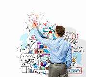 Businessman drawing sketches on wall. Back view image of businessman drawing sketches on wall Stock Image