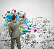 Businessman drawing sketches on wall. Back view image of businessman drawing sketches on wall Royalty Free Stock Photo