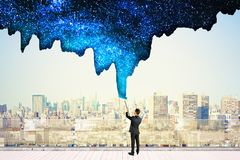 Businessman drawing sky. Businessman drawing beautiful starry sky on city background. Creativity and inspire concept royalty free stock images