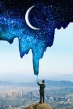 Businessman drawing sky. Businessman drawing beautiful starry sky with crescent on city background. Creativity and inspire concept stock photo