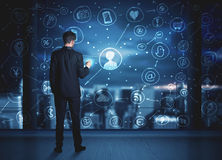 Businessman drawing social media connection scheme. On glass window with night cityscape background Royalty Free Stock Photo