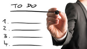 Businessman drawing up a to do list Stock Images