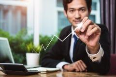 Businessman drawing upward. Businessman sitting at office drawing upward arrow up successful finance stock photography