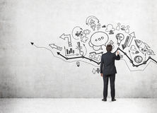 Businessman drawing on wall with sketches Royalty Free Stock Photo