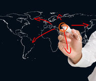 Businessman drawing world map with arrows. On black background Royalty Free Stock Photos