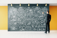 Businessman draws business development concept on blackboard Royalty Free Stock Photos