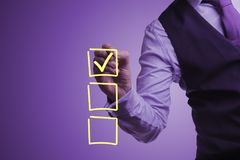 Businessman draws a checkmark in the selection box. Shooting in the Studio .A businessman in a waistcoat ,shirt and tie on a purple background draws a tick Royalty Free Stock Photo