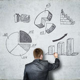Businessman draws on concrete wall of the business and financial figures. Business concept. Businessman draws on concrete wall of the business and financial Stock Images