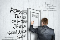 Businessman draws on concrete wall open door with flying off words. Business concept, work hard. Royalty Free Stock Image