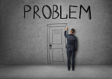 Businessman draws a door marked PROBLEM on the concrete wall. Royalty Free Stock Images