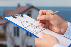 Businessman  draws a drawing of a house on the background of an Royalty Free Stock Photo