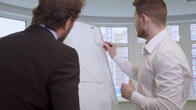 Businessman draws on the flip chart. Attractive young businessman drawing on the flip chart. Handsome bearded man in white shirt explaining something to his