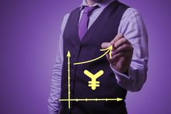 Businessman draws the growth of the Chinese yen. Shooting in the Studio .A businessman in a waistcoat ,shirt and tie on a purple background draws growth of the Royalty Free Stock Photo