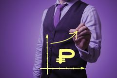 Businessman draws the growth of the growth of the Russian ruble. Shooting in the Studio .A businessman in a waistcoat ,shirt and tie on a purple background draws Stock Image