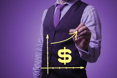 Businessman draws the growth of the us dollar. Shooting in the Studio .A businessman in a waistcoat ,shirt and tie on a purple background draws growth of the us Royalty Free Stock Photo