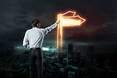 Businessman draws a light road sign Stock Image