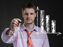 Businessman draws on a transparent screen graphics. Royalty Free Stock Images