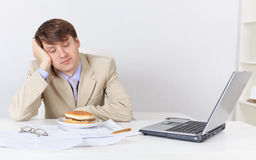 Businessman, dreamily looking at sandwich Stock Image