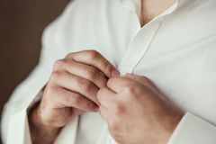 Businessman dress shirt. The man in the white shirt in the windo. W dress cufflinks. Politician, man`s style, Businessman buttoning his shirt,male hands closeup Stock Photos