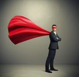 Businessman dressed as a superhero. Serious businessman dressed as a superhero in red mask and cloak over dark grey background royalty free stock image