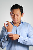 Businessman Dressing, Button Up His Shirt Sleeve. Photo image of a handsome attractive young Asian businessman dressing, button up his shirt sleeve. Wedding Stock Photography