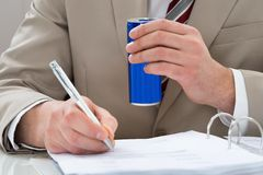Businessman with drink can and document Stock Photo