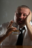 Businessman drinking alcohol and smoking cigarette Royalty Free Stock Image