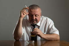 Businessman drinking alcohol and smoking cigarette Stock Images