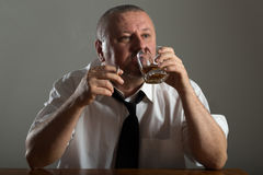 Businessman drinking alcohol and smoking cigarette Stock Photos