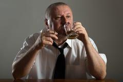 Businessman drinking alcohol and smoking cigarette Stock Photos