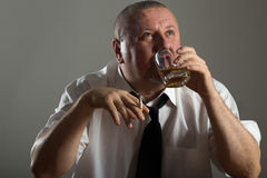 Businessman drinking alcohol and smoking cigarette Stock Photo