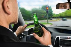 Businessman drinking beer while driving car Royalty Free Stock Photos