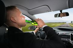 Businessman drinking beer while driving car Royalty Free Stock Image