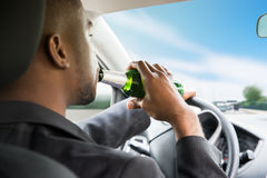 Businessman Drinking Beer While Driving Car. Side View Of A Young African Businessman Drinking Beer While Driving Car Royalty Free Stock Photo