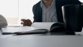 Businessman drinking coffe in the office, putting cup on the table. And writing in notebook. Indoors stock footage