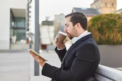 Man is drinking coffee and looking on Tablet PC royalty free stock images