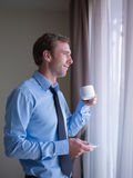 Businessman drinking coffee, looking out of window Stock Photography