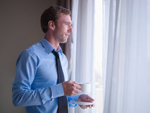 Businessman drinking coffee and looking outside Stock Image