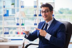 The businessman drinking coffee in the office during break. Businessman drinking coffee in the office during break Royalty Free Stock Photos